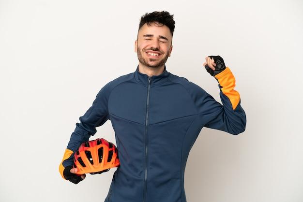 強いジェスチャーをしている白い背景で隔離の若いサイクリストの男