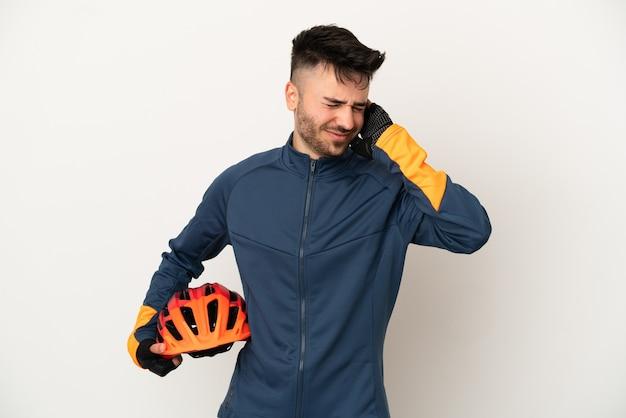 欲求不満と耳を覆っている白い背景で隔離の若いサイクリストの男
