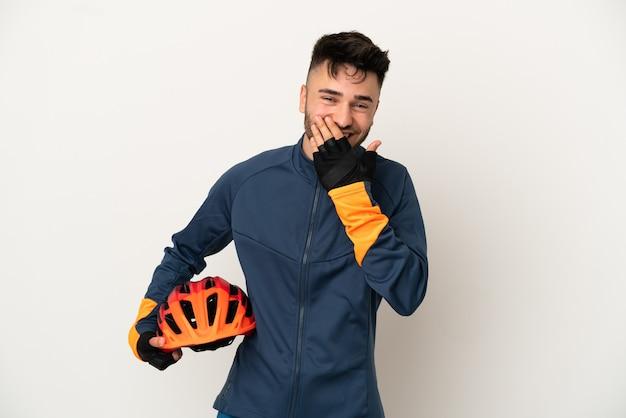 白い背景で隔離の若いサイクリストの男幸せと笑顔の手で口を覆う