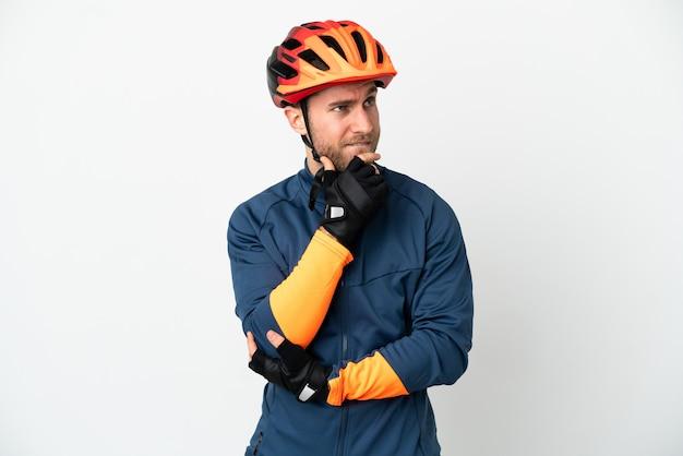 Молодой велосипедист человек изолирован на белом фоне, сомневаясь и думая