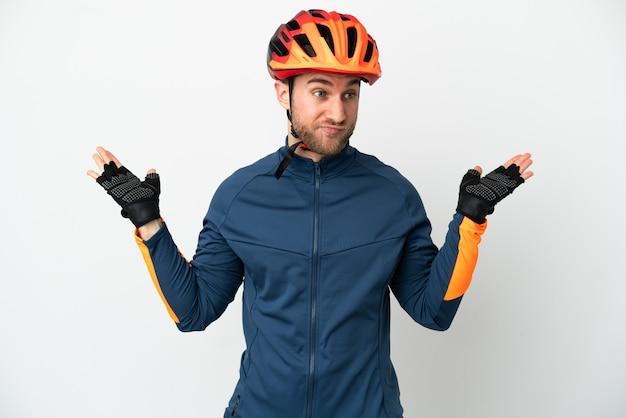 Молодой велосипедист человек изолирован на белом фоне, сомневаясь, поднимая руки