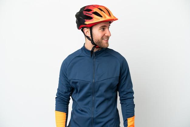Молодой велосипедист человек изолирован на белом фоне, глядя в сторону и улыбается