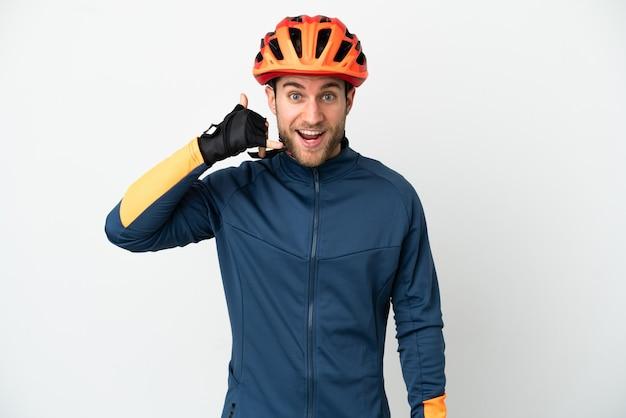 電話ジェスチャーを作る白い背景で隔離の若いサイクリストの男。コールバックサイン