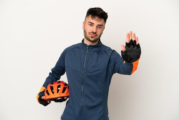 停止ジェスチャーを作る白い背景で隔離の若いサイクリストの男