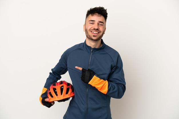 製品を提示する側を指している白い背景で隔離の若いサイクリストの男