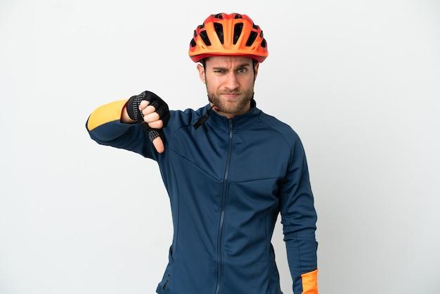 Молодой велосипедист человек изолирован на белом фоне, показывая большой палец вниз с отрицательным выражением лица