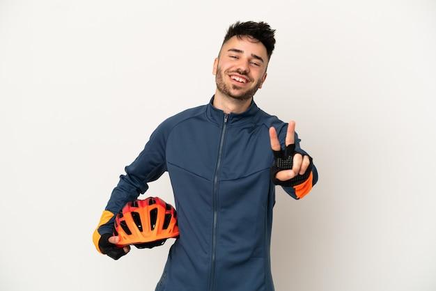 Молодой велосипедист человек изолирован на белом фоне улыбается и показывает знак победы