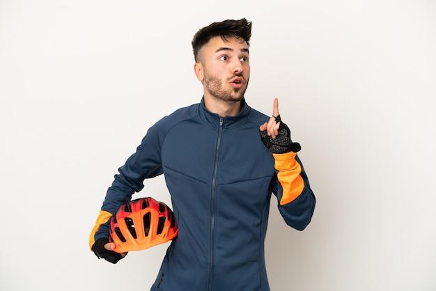 指を上に向けるアイデアを考えて白い背景で隔離の若いサイクリストの男