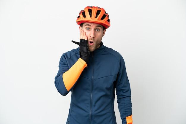 Молодой велосипедист, изолированные на белом фоне с удивленным и шокированным выражением лица