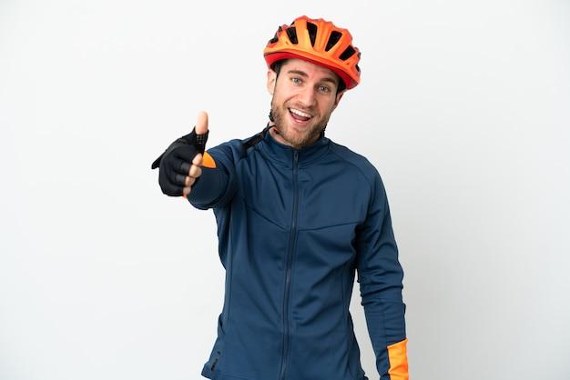 Молодой велосипедист, изолированные на белом фоне с большими пальцами руки вверх, потому что произошло что-то хорошее