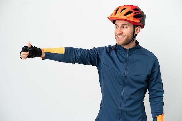 Молодой велосипедист мужчина изолирован на белой стене, показывая большой палец вверх жест