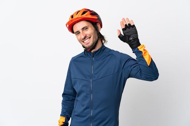 Молодой велосипедист мужчина изолирован на белой стене салютуя рукой с счастливым выражением лица