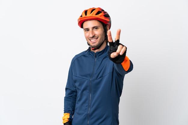 笑顔と勝利のサインを示す白い壁に孤立した若いサイクリストの男