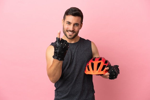 Young cyclist man isolated on pink background doing coming gesture