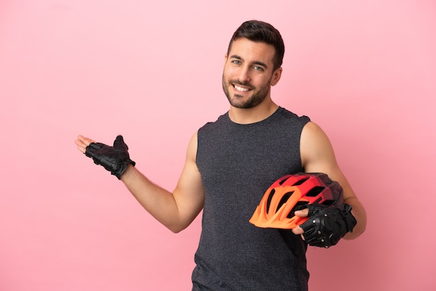 Young cyclist man isolated on pink background extending hands to the side for inviting to come