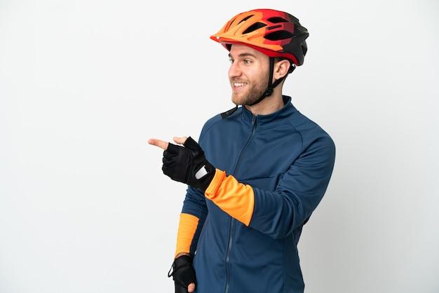Молодой велосипедист изолировал указывая пальцем в сторону и представляя продукт