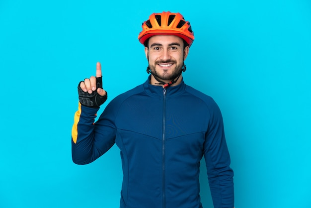 Young cyclist man isolated pointing up a great idea