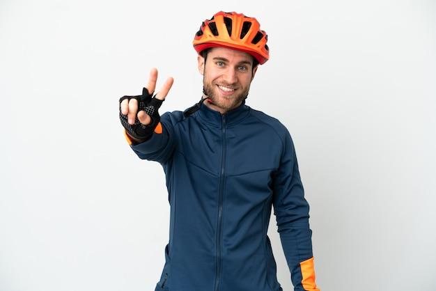 Молодой велосипедист человек изолирован, улыбаясь и показывая знак победы