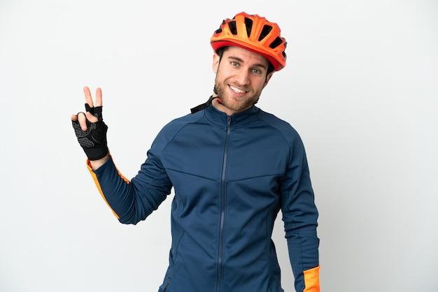 Молодой велосипедист человек изолирован, улыбаясь и показывая знак победы Premium Фотографии