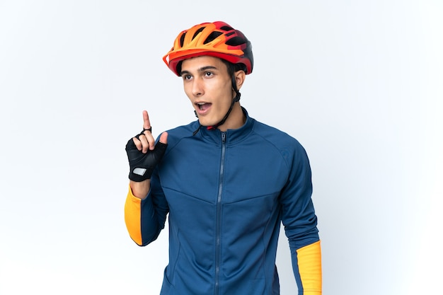 Young cyclist man isolated thinking an idea pointing the finger up
