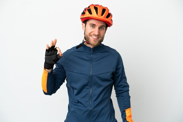 Young cyclist man isolated on white background showing ok sign with fingers