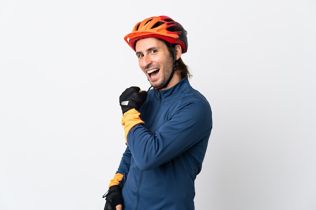 Young cyclist man isolated on white celebrating a victory