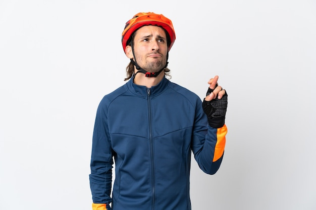 Young cyclist man isolated on white with fingers crossing and wishing the best