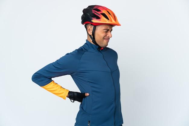Молодой велосипедист человек позирует изолирован у глухой стены