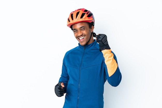 Young cyclist man with braids over isolated background celebrating a victory