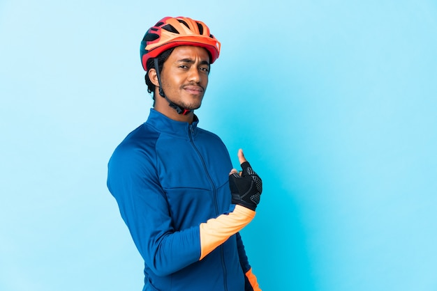 Young cyclist man with braids over isolated background proud and self-satisfied