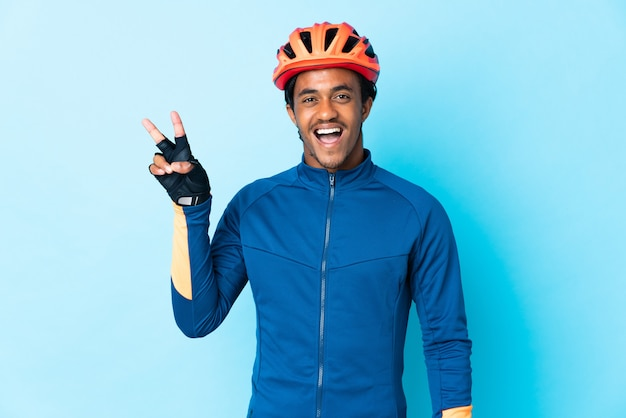 Young cyclist man with braids over isolated background smiling and showing victory sign