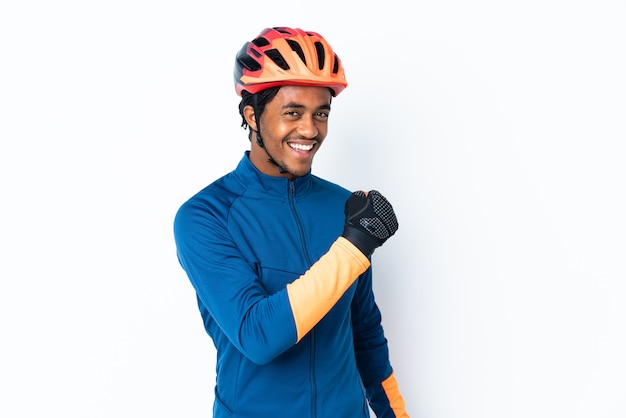 Young cyclist man with braids over isolated wall celebrating a victory