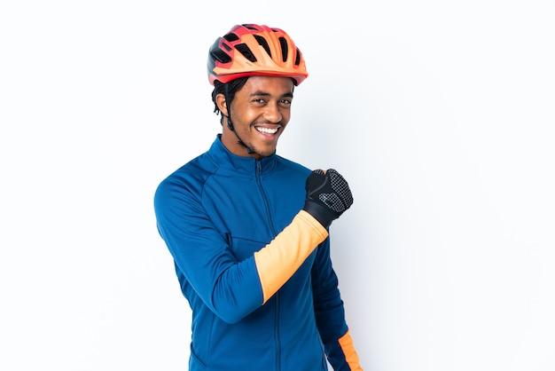 勝利を祝う孤立した壁の上に三つ編みを持つ若いサイクリストの男