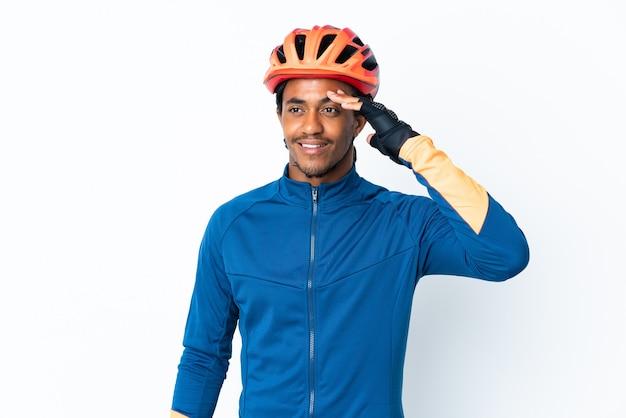 幸せな表情で手で敬礼する上に三つ編みの若いサイクリストの男