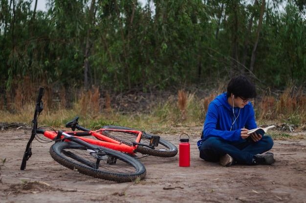 Young cyclist reading a book in the forest, resting on the ground next to his bike, active lifestyle.
