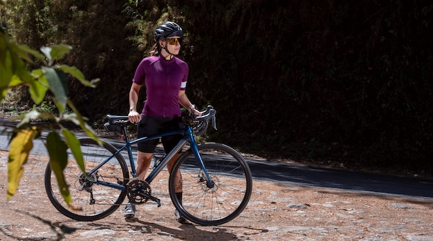Молодой велосипедист отдыхает со своим велосипедом на обочине дороги в шлеме и солнцезащитных очках