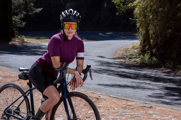 Young cyclist resting with his bicycle on the side of the road wearing helmet and sunglasses