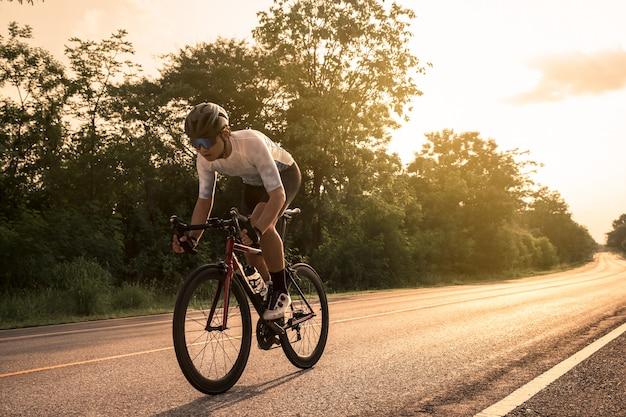 일몰에 열린 길에서 자전거를 타는 젊은 사이클