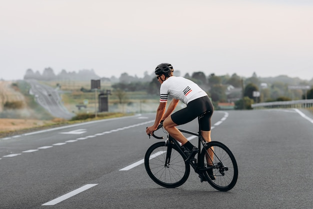Молодой велосипедист со спортивным телом, одетый в спортивную одежду, мчится по дороге в летний день