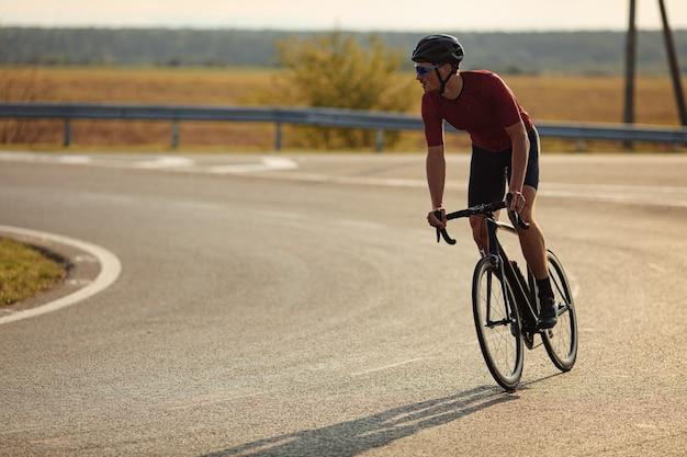 시골 사이에서 아스팔트 도로에 근육질 몸매 승마 자전거와 젊은 사이클.
