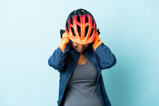 Young cyclist woman isolated on blue background frustrated and covering ears