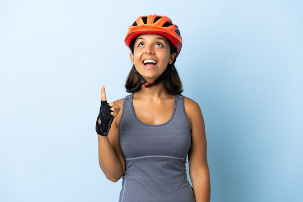 Young cyclist woman isolated on blue pointing up and surprised