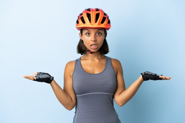 Young cyclist woman isolated on blue with shocked facial expression