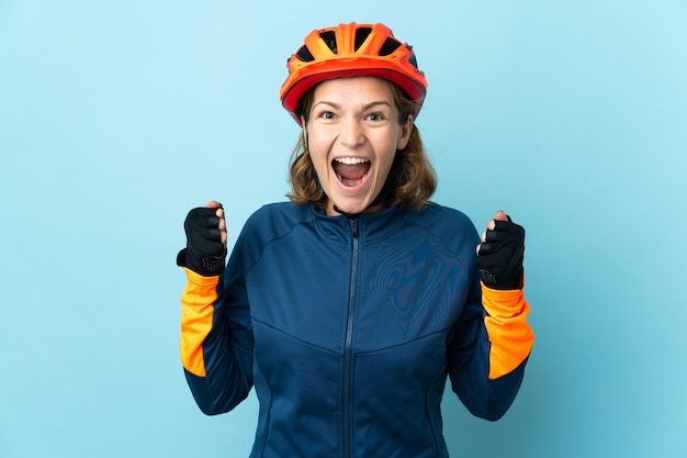 Изолированная молодая велосипедистка празднует победу в победном положении