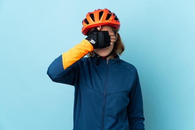손으로 눈을 덮고 파란색 배경에 고립 된 젊은 사이클 여자. 뭔가보고 싶지 않아