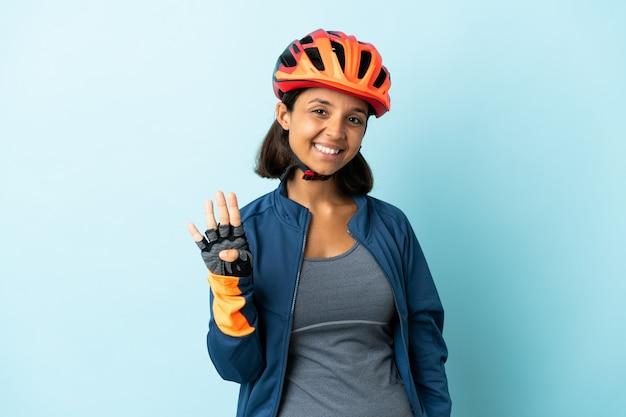 幸せな青い背景で隔離の若いサイクリストの女性と指で4を数える