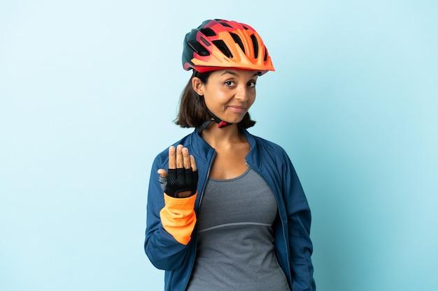 Женщина молодой велосипедист, изолированные на синем фоне, приглашая прийти с рукой. счастлив что ты пришел