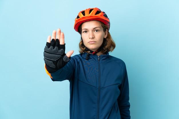Женщина молодой велосипедист, изолированные на синем фоне, делая жест остановки