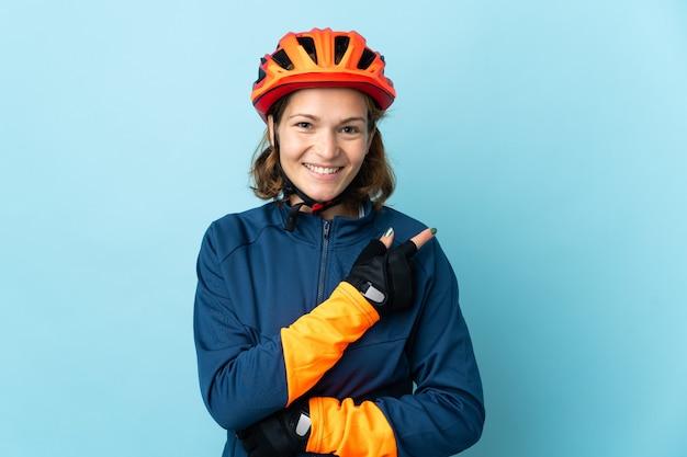 Молодая женщина-велосипедист изолирована на синем фоне, указывая в сторону, чтобы представить продукт