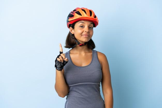 若いサイクリストの女性が指を示して持ち上げて青い背景で隔離
